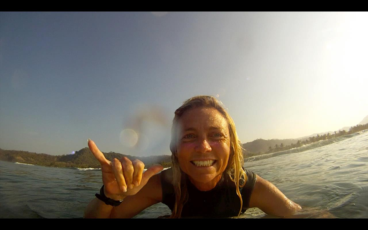 Jennifer Faith gives a hang ten from her surfboard to encourage battered women of all faiths